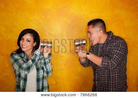 Hispanic Man and Woman Communicate Through Tin Cans