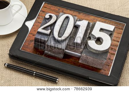 2015  - New Year concept  - number in vintage metal type printing blocks on a digital tablet with a cup of coffee