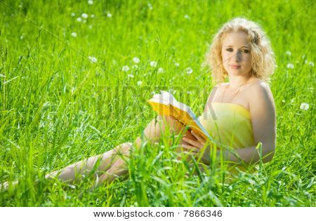 Girl Reading Book In Grass
