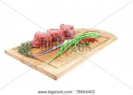 fresh meat : raw beef fillet on wooden board with thyme and red hot dry pepper ready to prepare . isolated over white background
