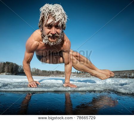 Man with frozen hair doing yoga exercise (parsva bakasana) on the ice