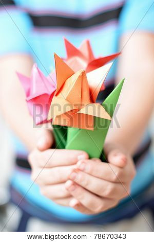 Bouquet of origami tulips in children's hands