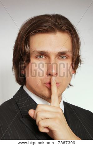 Businessman in suit shows silence