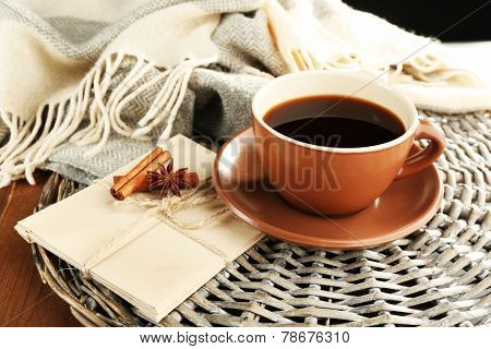 Cup of coffee with envelopes on wicker stand on wooden table background