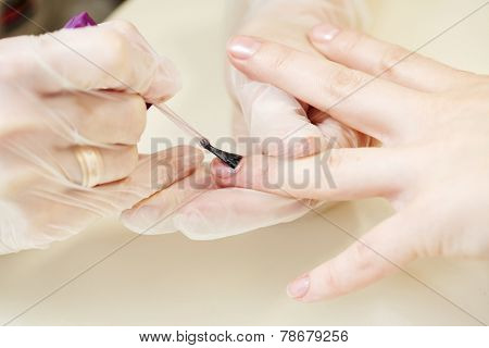 Manecurist perfoming finger nail procedure for hand care in beauty salon