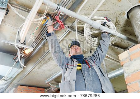 line electrician builder engineer worker at indoor construction site cabling