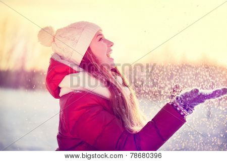 Beauty Winter Girl Blowing Snow in frosty winter Park. Outdoors. Flying Snowflakes. Sunny day. Backlit. Joyful Beauty young woman Having Fun in Winter Park