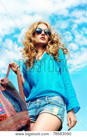 Gorgeous young woman with beautiful wavy hair wearing casual blouse and jeans shorts posing outdoor. Fashion shot.