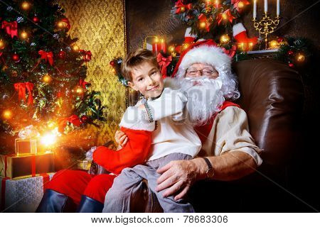 Happy little boy sitting on the lap of Santa Claus and rejoice a gift. Christmas decoration.