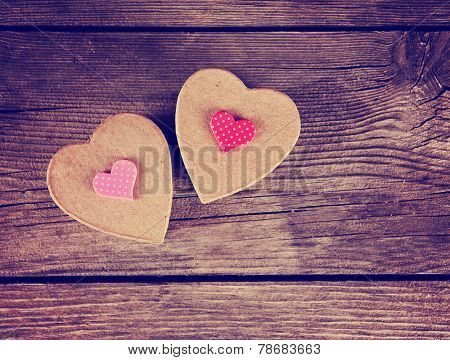 a valentine's day heart on a wooden background toned with a retro vintage instagram filter effect