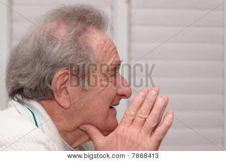 Smiling elderly man resting his head on hands profile closeup