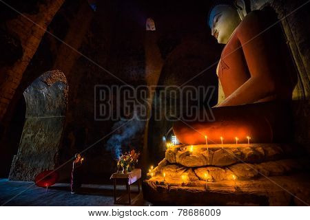 Unidentified little Monk pray the respect to Lord Buddha in old temple