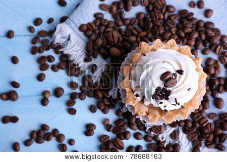 Cake with cream and spilled coffee beans on blue wooden background with jeans material