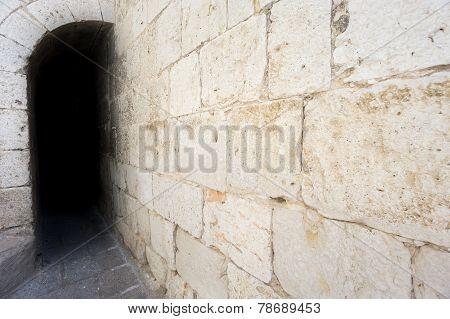 Dark passage with antique stone wall