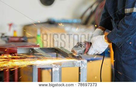 Worker Grinding Steel By Grinding Machine