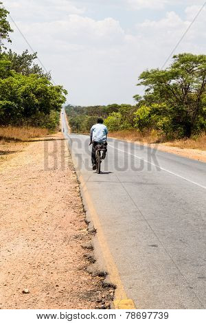 Local Man Riding On A Bike On A Desolated Road