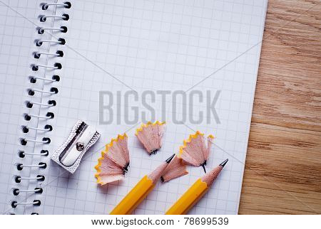 Pencils, Pencil Sharpener And Unfolded Notebook On Office Desk
