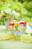 picture of elderflower  - Bottles with elderflower syrup in the garden - JPG