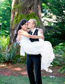 stock photo of biracial  - Caucasian groom carrying his biracial bride outdoors with a kiss - JPG