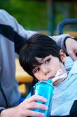 stock photo of biracial  - Disabled biracial little boy in wheelchair drinking water from sippy cup - JPG