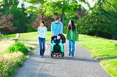 foto of babysitter  - Disabled boy in wheelchair walking with family outdoors on sunny day in park - JPG