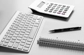 stock photo of field mouse  - Office desk with keyboard ballpoint spiral notebook and calculator with shallow depth of field - JPG