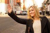 pic of hail  - a beautiful young woman hailing a taxi - JPG