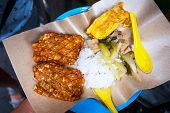 stock photo of crispy rice  - Indonesian tempe with rice and curry sauce served in paper from local market - JPG