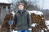 picture of early-man  - man with a fork  heap of manure in early spring - JPG