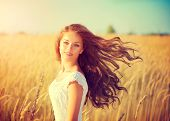 stock photo of blowing  - Beauty Girl Outdoors enjoying nature - JPG