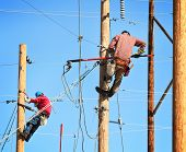 picture of utility pole  - two electrical linemen working on lines - JPG