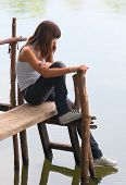picture of dock  - Sad lonely teenage girl sitting on the small wooden dock on the river - JPG