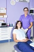 stock photo of dental  - portrait of a smiling dental assistant standing and a female patient sitting on the dental chair at the cabinet of the dental clinic - JPG