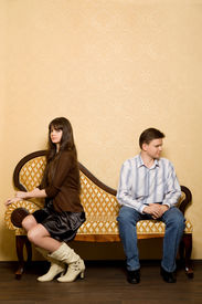 stock photo of conflict couple  - young beautiful woman and young man sitting on sofa in room have taken offence against each other - JPG