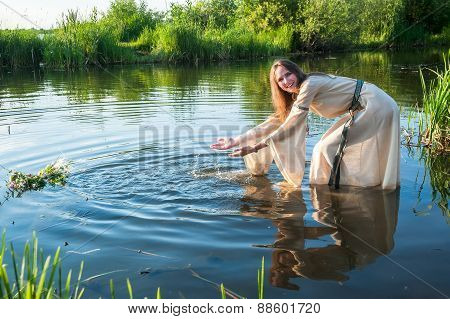 Attractive funny girl lowers wreath in water