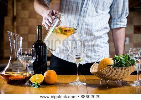 Man pours white homemade sangria