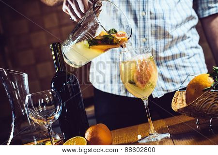 Man pours white homemade sangria