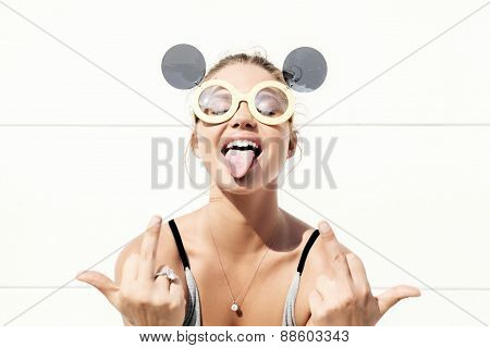 Young Woman In Sunglasses Showing Tongue And Middle Finger