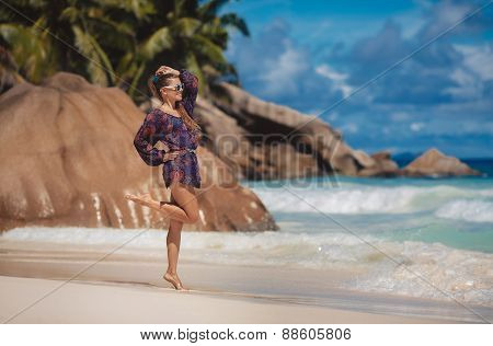 Beautiful and fashion young woman with long legs in short dress posing on a tropical beach