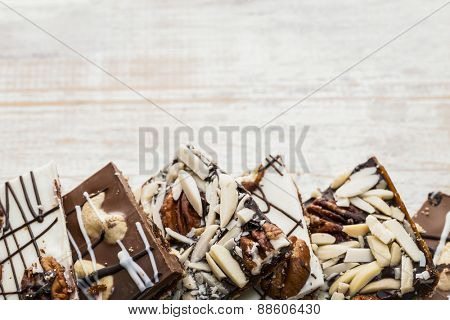 Assorted chocolate caramel bark pieces arranged on wooden background from above with copy space