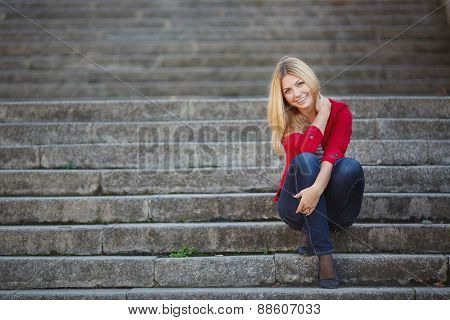 Portrait of a woman sitting on the steps in the city.