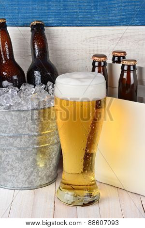 Beer still life with a tall glass a six pack and ice bucket full of cold bottles. Vertical format on a rustic wood set.