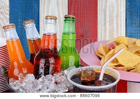 Cold soda bottles, cups and chips against a red white and blue background. Patriotic picnic image for 4th of July or Memorial Day projects.