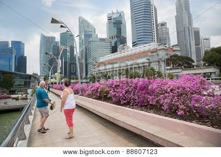 SINGAPORE - FEBRUARY 18, 2015: European tourists on the Esplanade Drive with views of Central Business District in Singapore. This area a popular holiday destination for locals and tourists.