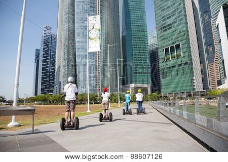 SINGAPORE - CIRCA FEBRUARY 2015: Young people ride on an electric scooter along the waterfront Marina Bay in Singapore. Quay Marina Bay a popular place for walks among the tourists and locals.