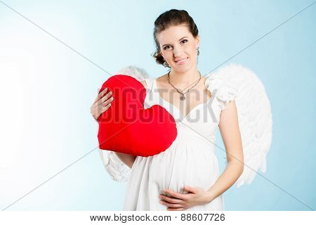 Portrait of a beautiful angelic pregnant woman with a red heart in hands