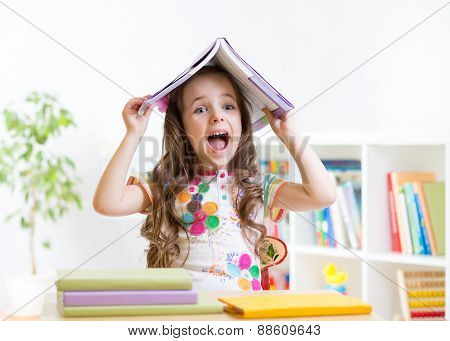 smiling child with a book over her head in primary school