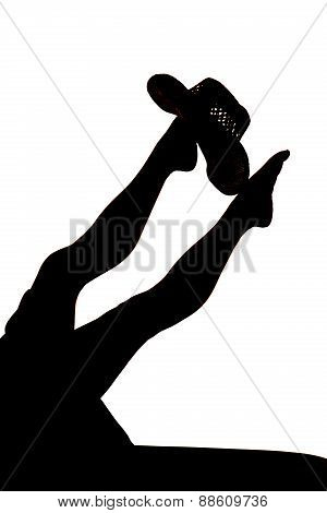 Silhouette Of Womans Legs With Cowboy Hat Up On Foot Legs Out