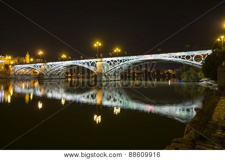 Night View Of The Triana Bridge In Seville, Spain. Also Called Isabel Ii Bridge.