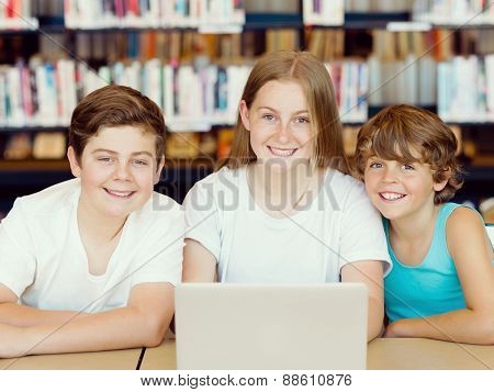 Three kids in library with notebook